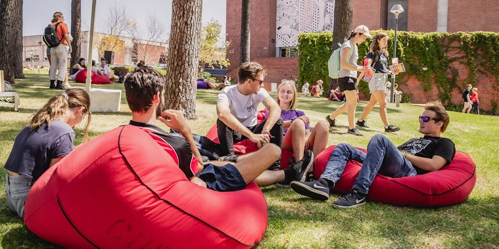 A group of students sitting in red beanbags under the pine trees at Curtin