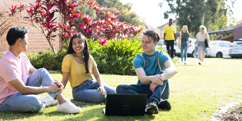 Students sitting on grass.