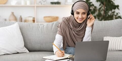 Female student at a laptop wearing headphones.